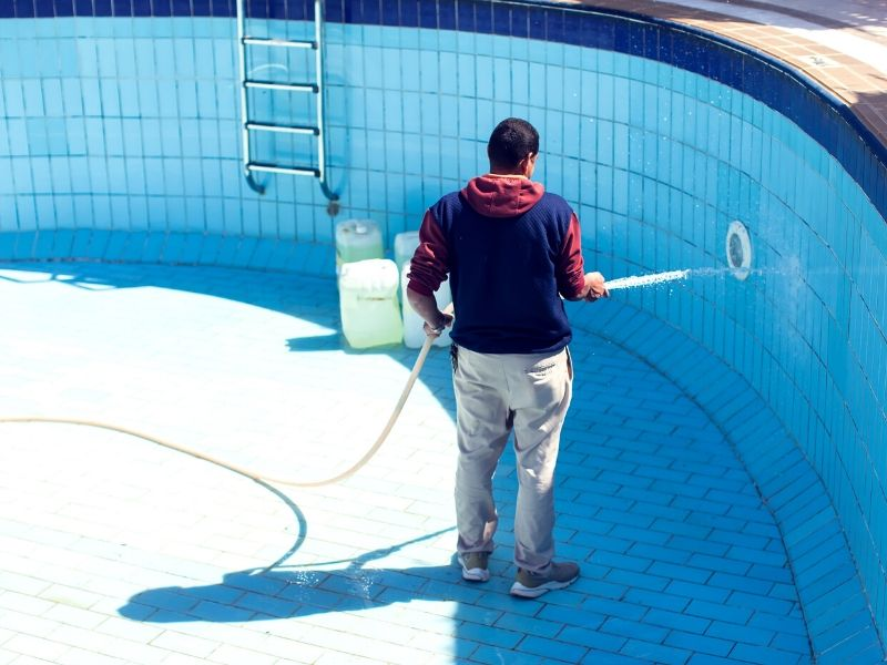 professional pool cleaner is cleaning the pool pump and other pool equipment